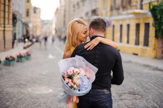 Młoda i piękna blondynki kobieta trzyma bukiet kwiaty i ściska mężczyzna Premium Zdjęcia