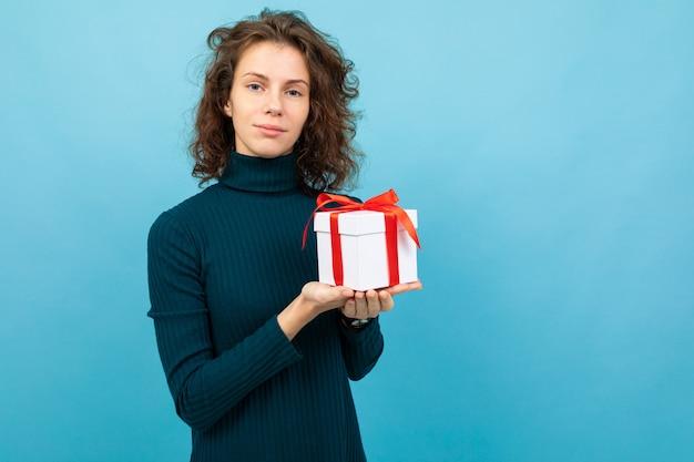 Młoda I Piękna Caucasian Dziewczyna Z Kręconymi Włosami Utrzymuje Białe Pudełko Z Czerwoną Wstążką I Uśmiecha Się, Portret Na Niebieskim Tle Premium Zdjęcia