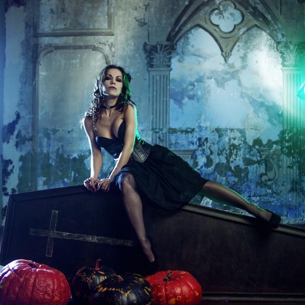 Młoda i seksowna kobieta, wizerunek czarownic na cmentarzu siedzącym na trumnie wiekowej. Premium Zdjęcia