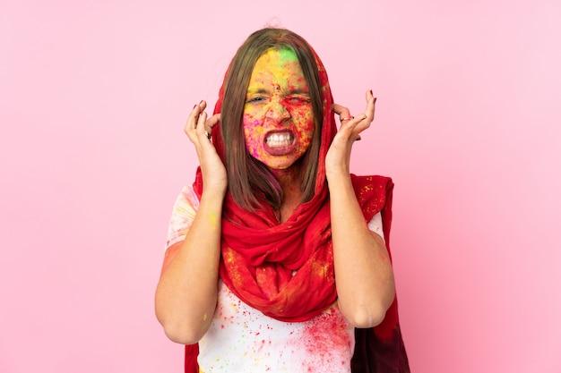 Młoda Indianka Z Kolorowymi Pudrami Holi Na Twarzy Na Różowej ścianie Sfrustrowana I Zakrywająca Uszy Premium Zdjęcia