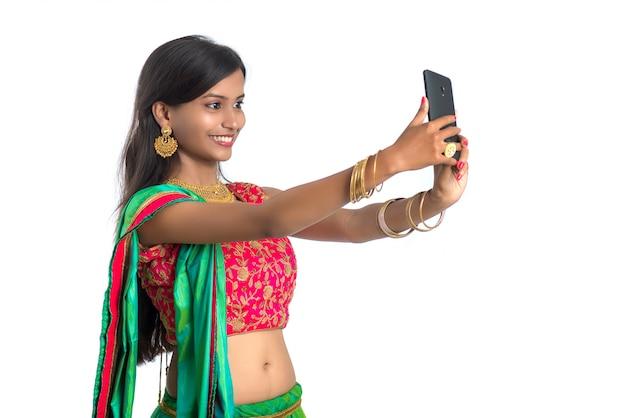 Młoda Indiańska Kobieta Używa Telefon Komórkowego Lub Smartphone, Opowiada Selfie Lub Opowiada Na Wideo Gadce Odizolowywającej Na Białej ścianie Premium Zdjęcia