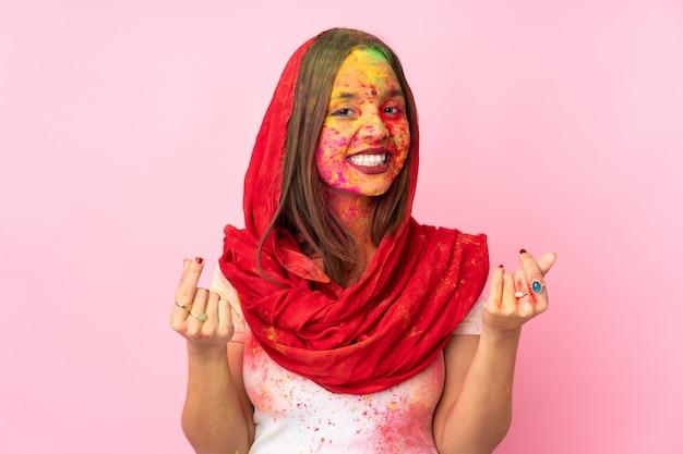Młoda Indiańska Kobieta Z Kolorowymi Holi Proszkami Na Jej Twarzy Odizolowywającej Na Menchii ścianie Robi Pieniądze Gestowi Premium Zdjęcia
