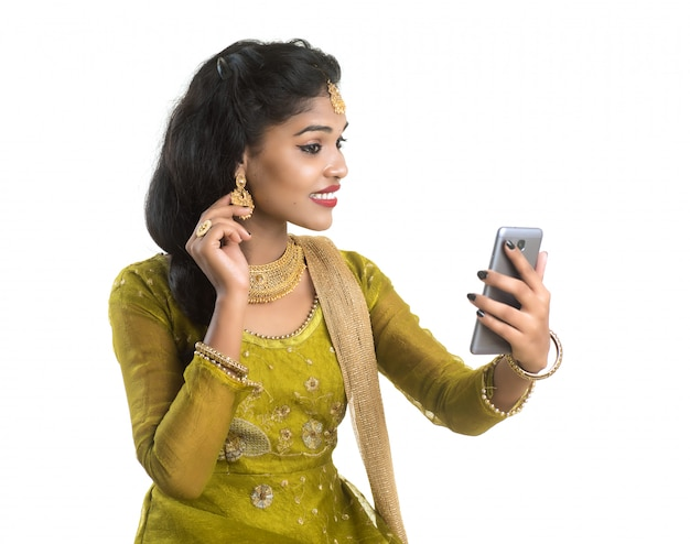 Młoda Indiańska Tradycyjna Dziewczyna Używa Telefon Komórkowego Lub Smartphone Odizolowywających Na Białej ścianie Premium Zdjęcia