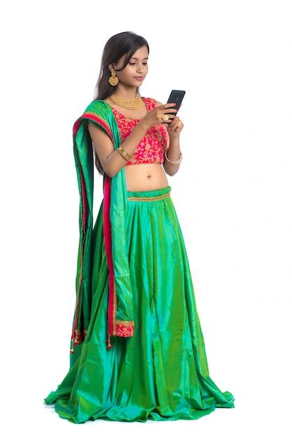 Młoda Indiańska Tradycyjna Dziewczyna Używa Telefon Komórkowego Lub Smartphone Odizolowywających Na Bielu Premium Zdjęcia