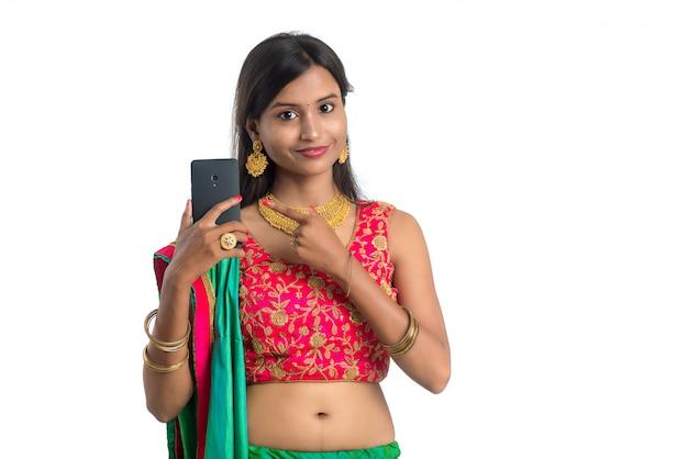 Młoda Indiańska Tradycyjna Kobieta Używa Telefon Komórkowego Lub Smartphone Odizolowywających Na Białej ścianie Premium Zdjęcia