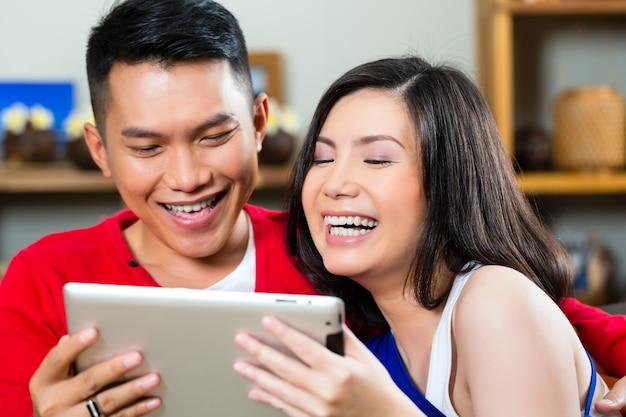 Młoda indonezyjska para - mężczyzna i kobieta - siedząca z komputerem typu tablet na kanapie Premium Zdjęcia
