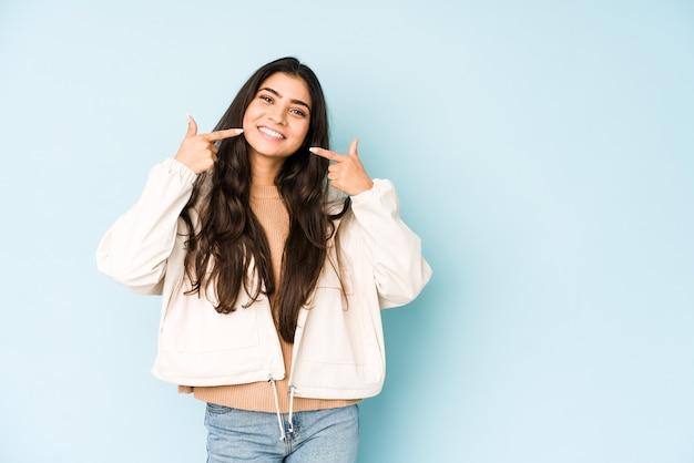 Młoda Indyjska Kobieta Na Niebieskiej Przestrzeni Uśmiecha Się, Wskazując Palcami Na Usta. Premium Zdjęcia
