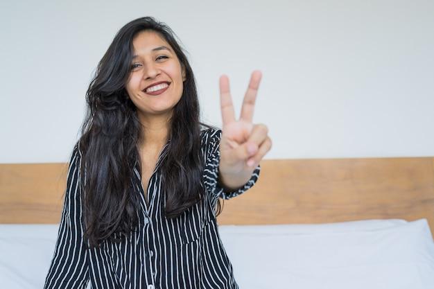 Młoda Indyjska Kobieta Robi Zwycięstwo Gestowi W Sypialni Premium Zdjęcia
