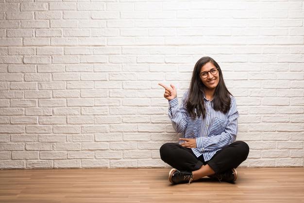 Młoda indyjska kobieta siedzi przeciw ściana z cegieł wskazuje strona, ono uśmiecha się zaskakuję przedstawiać coś, naturalny i przypadkowy Premium Zdjęcia