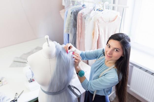 Młoda Indyjska Krawcowa O Długich Czarnych Włosach Tworzy Nową Sukienkę Z Piórami Na Manekinie Do Szycia Premium Zdjęcia