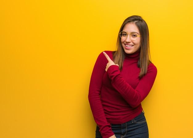 Młoda Intelektualna Kobieta Ono Uśmiecha Się I Wskazuje Z Boku Premium Zdjęcia