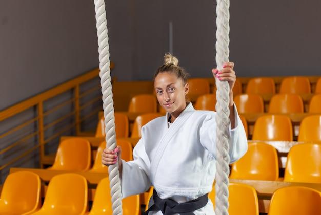 Młoda Judoka Kobieta W Białym Kimonie I Czarnym Pasie Pozuje W Hali Sportowej Premium Zdjęcia