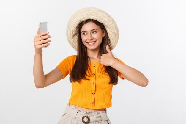 Młoda Kaukaska Kobieta Cieszy Się Selfie Z Ona Odizolowywającą Na Białym Lato Podróży Pojęciu. Premium Zdjęcia