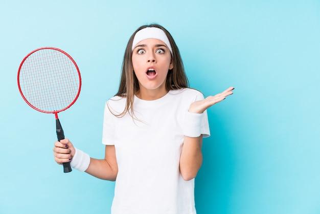 Młoda Kaukaska Kobieta Gra W Badmintona Na Białym Tle Zaskoczony I Zszokowany. Premium Zdjęcia