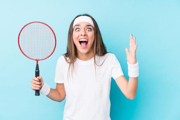 Młoda Kaukaska Kobieta Grająca W Badmintona Na Białym Tle Otrzymała Miłą Niespodziankę, Podekscytowana I Podnosząc Ręce. Premium Zdjęcia