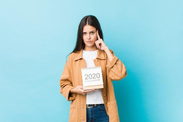 Młoda Kaukaska Kobieta Trzyma Kalendarz 2020 Roku, Wskazując Palcem świątynię, Myśląc, Skupiając Się Na Zadaniu. Premium Zdjęcia