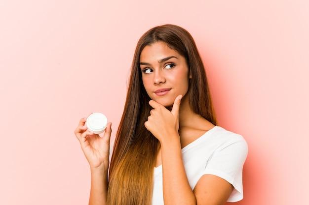 Młoda Kaukaska Kobieta Trzyma Krem Nawilżający, Patrząc W Bok Z Wątpliwym I Sceptycznym Wyrazem Twarzy. Premium Zdjęcia