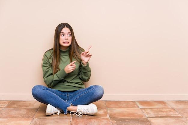 Młoda Kaukaski Kobieta Siedzi Na Podłodze Na Białym Tle Zszokowany Wskazując Palcami Wskazującymi Na Miejsce. Premium Zdjęcia