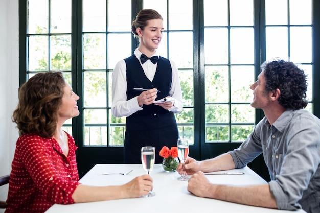 Młoda kelnerka bierze zamówienie od pary Premium Zdjęcia
