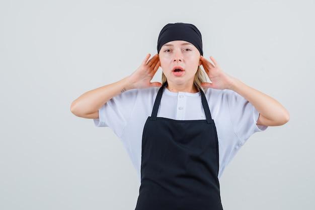 Młoda Kelnerka Opierająca Palce Na Uszach W Mundurze I Fartuchu I Wyglądająca Na Zirytowaną Darmowe Zdjęcia