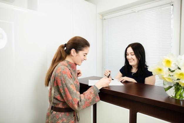 Młoda kobieta administrator w klinice dentystycznej w miejscu pracy. wstęp klienta Premium Zdjęcia