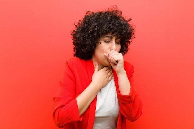 Młoda kobieta afro mdłości z bólem gardła i objawami grypy, kaszel z zakrytymi ustami Premium Zdjęcia