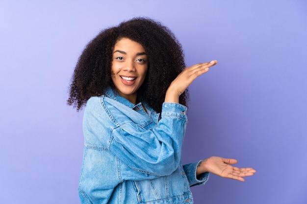 Młoda Kobieta Afroamerykanów Na Białym Tle Na Fioletowy Trzymając Copyspace, Aby Wstawić Reklamę Premium Zdjęcia