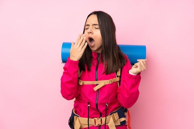 Młoda Kobieta Alpinista Z Dużym Plecakiem Na Pojedyncze Różowe ściany Ziewanie I Obejmujące Szeroko Otwarte Usta Ręką Premium Zdjęcia
