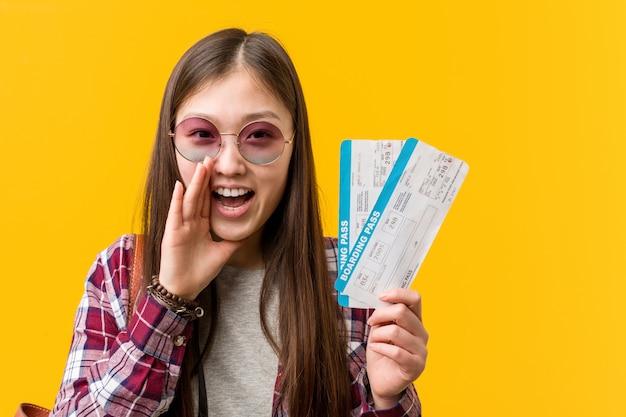 Młoda kobieta azjatyckich gospodarstwa bilety lotnicze krzyczy podekscytowany do przodu. Premium Zdjęcia