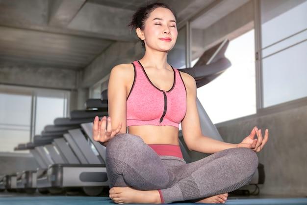 Młoda Kobieta Azji Praktykowania Jogi Na Siłowni. Lotus Stanowią Na Sesji Medytacyjnej. Premium Zdjęcia