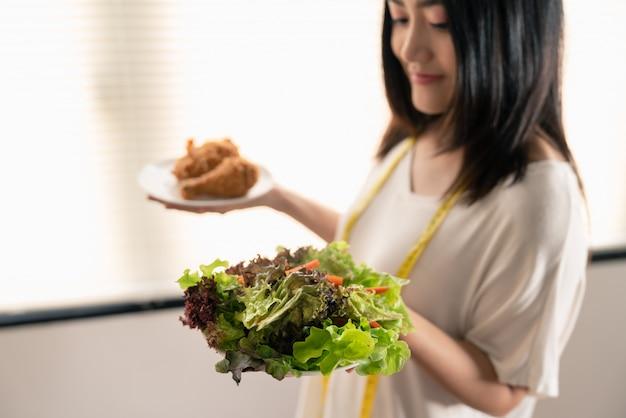 Młoda kobieta azji schudnąć, wybierając między sałatka jarzynowa i fast foodów smażonego kurczaka w naczyniach na rękę Premium Zdjęcia