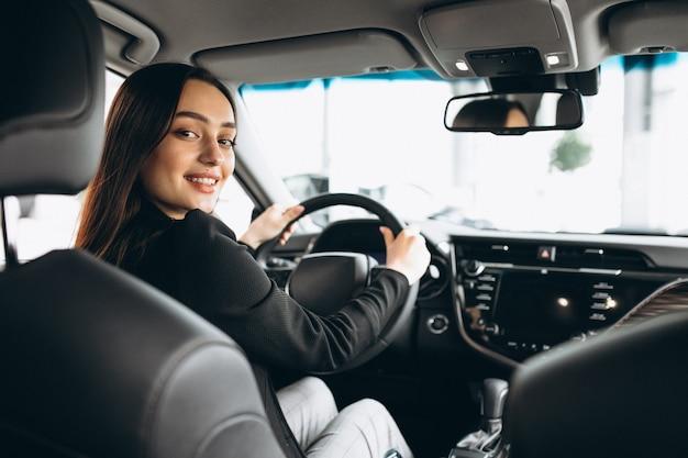 Młoda kobieta bada samochód w samochodowej sala wystawowej Darmowe Zdjęcia