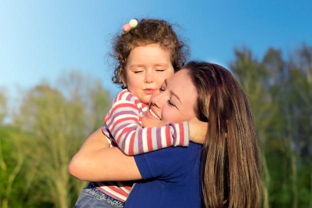 Młoda Kobieta Baw Się Dobrze, Przytulanie Jej Słodkie Dziecko Dziewczynka. Portret Matki, Małe Dziecko Córka Outdoors Przy Lato Słonecznym Dniem. Dzień Matki, Miłość, Szczęście, Rodzina, Rodzicielstwo, Koncepcja Dzieciństwa Premium Zdjęcia