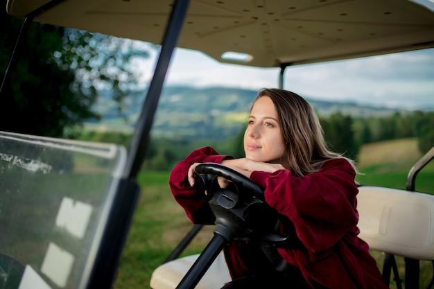 Młoda Kobieta Bawić Się Z Golfowym Buggy Samochodem Na Polu W Górach Premium Zdjęcia