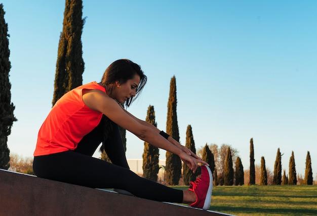 Młoda kobieta biegacz rozciąganie nogi przed uruchomieniem w parku. Premium Zdjęcia