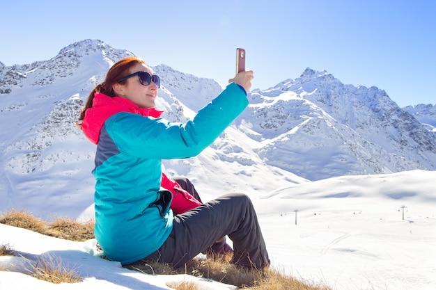 Młoda kobieta bierze selfie na swoim telefonie na pięknym szczycie góry. zimowy czas Premium Zdjęcia