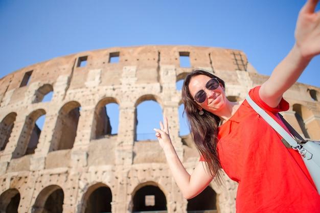 Młoda Kobieta Bierze Selfie Portret Przed Colosseum W Rzym, Włochy. Szczęśliwa Dziewczyna Na Wakacjach Premium Zdjęcia