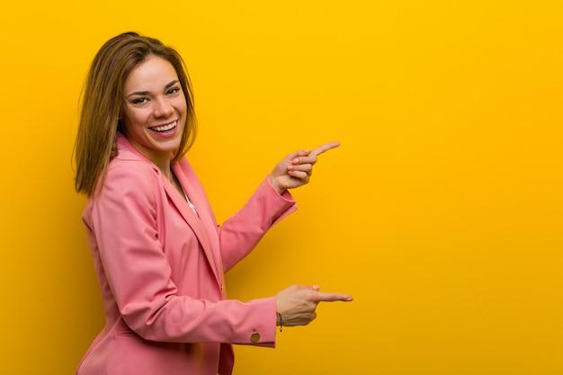 Młoda Kobieta Biznesu Mody Podekscytowany, Wskazując Palcami Z Dala. Premium Zdjęcia
