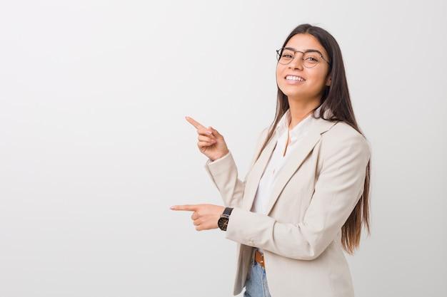 Młoda Kobieta Biznesu Podekscytowany, Wskazując Palcami Daleko Premium Zdjęcia