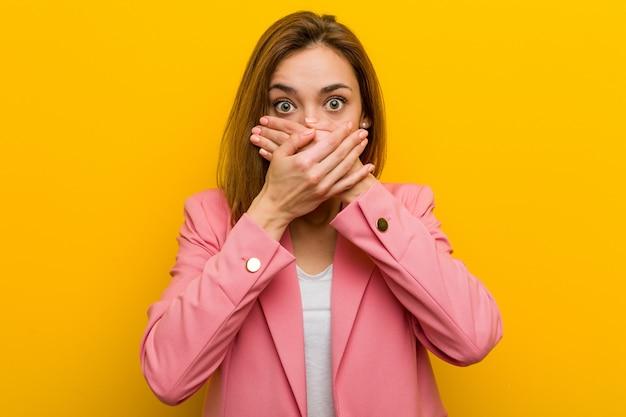 Młoda kobieta biznesu szokujące usta obejmujące ręce. Premium Zdjęcia