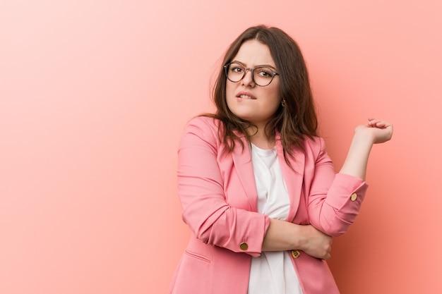 Młoda kobieta biznesu wielkości plus kaukaski dotykając tylnej głowy, myślenia i dokonywania wyboru. Premium Zdjęcia