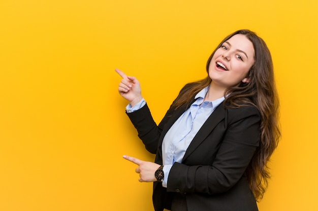 Młoda Kobieta Biznesu Wielkości Plus Podekscytowana, Wskazując Palcami Z Dala Premium Zdjęcia