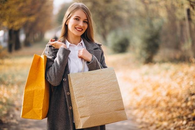 Młoda kobieta chodzi w parku z torba na zakupy Darmowe Zdjęcia