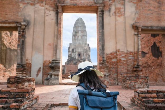 Młoda kobieta chodzi w starej świątyni w phra nakhon si ayutthaya, tajlandia na relaksujący dzień. Premium Zdjęcia