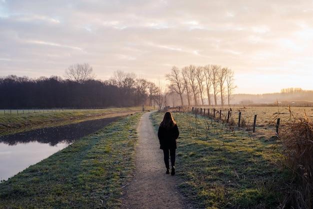 Młoda Kobieta Chodzi W Zimny Dzień Rzeką W Zmierzchu, Piękny Krajobrazowy Tło Kolorowy Premium Zdjęcia