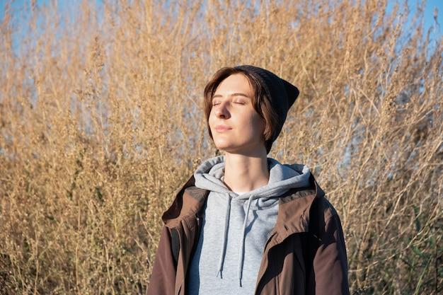 Młoda Kobieta Cieszy Się Jesiennym Słońcem. Kobieta W Kurtce Na Zewnątrz W Jasne Słoneczne Popołudnie Premium Zdjęcia
