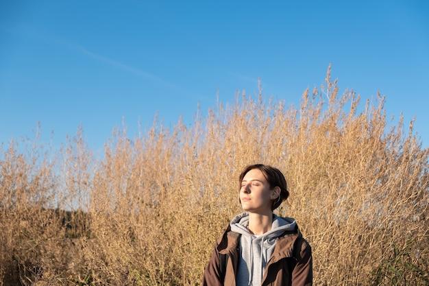 Młoda Kobieta Cieszy Się Jesiennym Słońcem. Kobieta W Parka Na Zewnątrz Na łące W Jasne Słoneczne Popołudnie Premium Zdjęcia