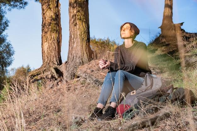 Młoda Kobieta Cieszy Się Piękną Jesienną Pogodą. Kobieta Turysta Siedzi Pod Sosnami W Słoneczne Popołudnie Premium Zdjęcia