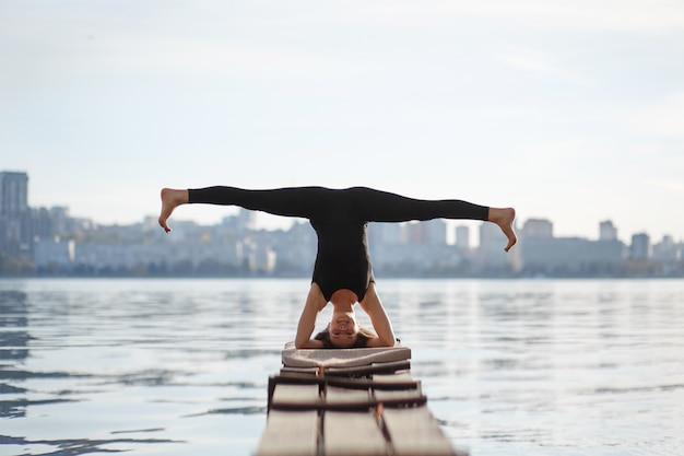 Młoda Kobieta ćwiczy ćwiczenia Jogi Przy Cichym Drewnianym Molo Z Miastem Sport I Rekreacja W Pośpiechu Miasta Premium Zdjęcia
