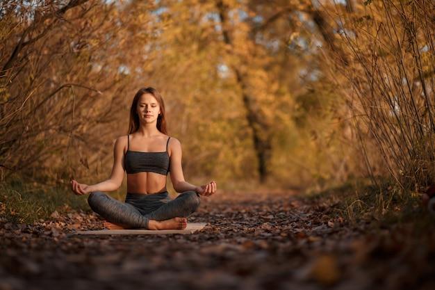 Młoda Kobieta ćwiczy Joga ćwiczenie Przy Jesień Parkiem Z żółtymi Liśćmi. Sport I Rekreacja W Stylu życia Premium Zdjęcia